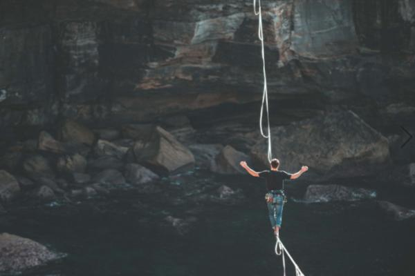 Person walking on a tightrope across a canyon