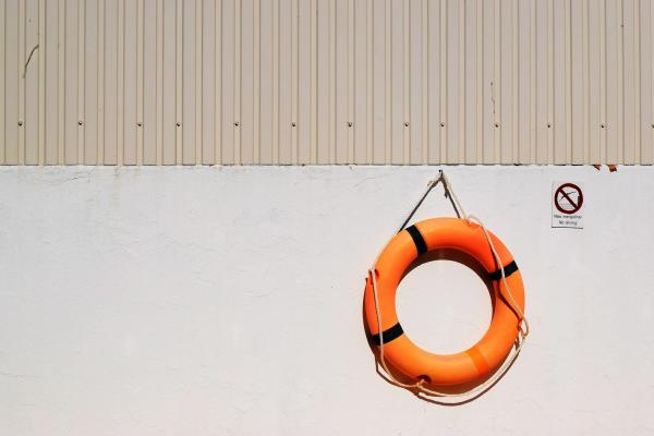 Photograph of a wall with a liferaft hanging off of it